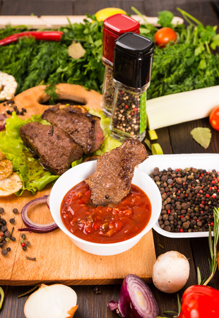 bounty: High Angle Close Up View of Small Pieces of Beef with Bowl of Salsa Dip Surrounded by Fresh Peppercorns, Herbs and Bounty of Colorful Vegetables Foto de archivo