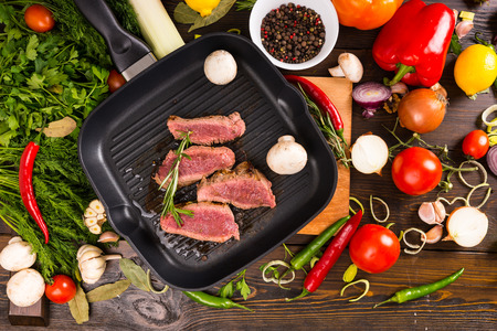 bounty: High Angle View of Rare Seasoned Sliced Beef Sizzling in Hot Frying Pan Surrounded by Bounty of Ingredients - Colorful Vegetables and Fresh Herbs and Spices