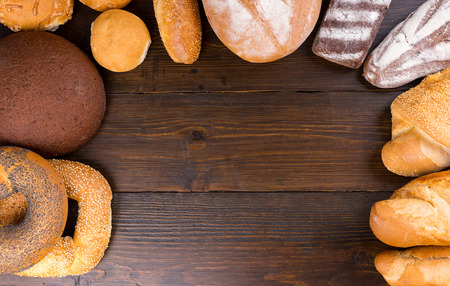french bread rolls: Top down view on dark wood paneled table with blank center surrounded by freshly baked french bread, rolls, bagels and baguettes