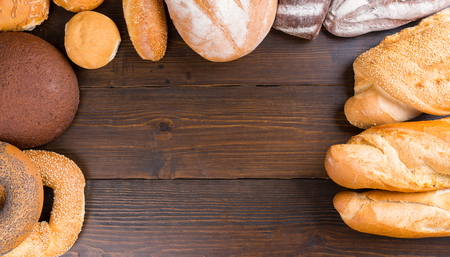 french bread rolls: Top down view on dark wooden table with copy space surrounded by freshly baked french bread, rolls, bagels and baguettes