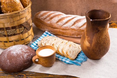 ornately: Ornately decorated wooden pitcher, little cup of milk and freshly baked bread as whole loaf and slices next to basket on table