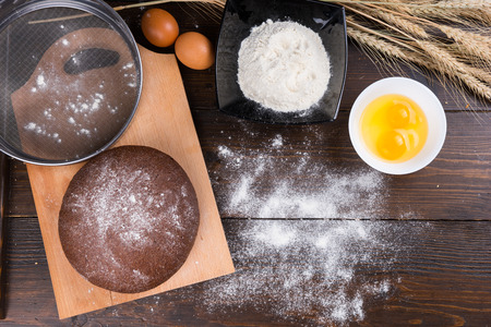 Top down view on baking ingredients of eggs, yolks, fine white flour, stalks of dried wheat rye roll and large sifter on top of cutting board