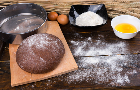 sifter: Delicious round loaf of baked rye bread on cutting board next to flour sifter, bowls and eggs on wooden table