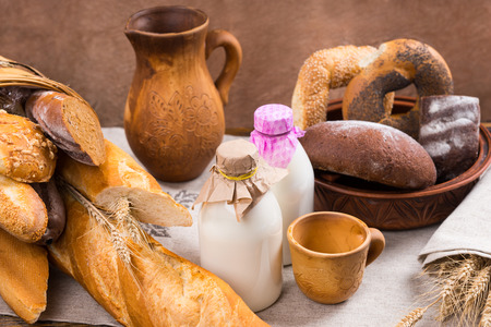 Pair of glass bottles of milk, tall wooden pitcher, little cup and assorted bread loaves in background on table