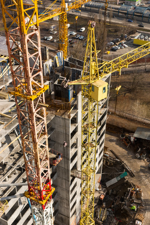 immense: Immense tall tower cranes next to concrete high rise apartment buildings under construction in urban area