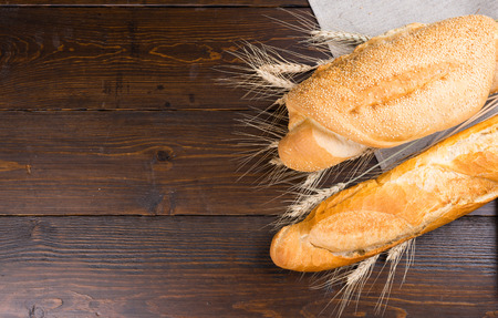 slits: Two types of baguette loaves with slits on top and sesame seeds in between whole wheat stalks over dark brown table