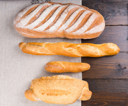 slits: Top down view of various sized baguettes with flour coating, sesame seeds and slits on top over bakery paper and wooden table