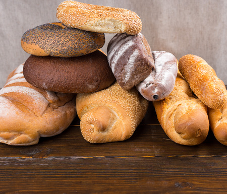 french bread rolls: Tall stack stack of bagels topped with sesame and poppy seeds over large rolls of leavened white french bread rolls