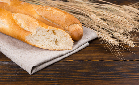 cut through: Sliced fresh French baguette cut through to show the texture alongside fresh ripe ears of wheat on a rustic wooden table, close up view