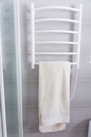 shower cubicle: Towel hanging on a heated wall mounted white metal electrical towel rack against a grey tiled bathroom wall
