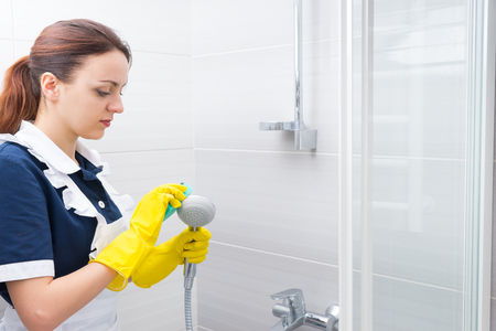 held down: Serious young female housekeeper scrubbing down hand held shower head surface with green sponge