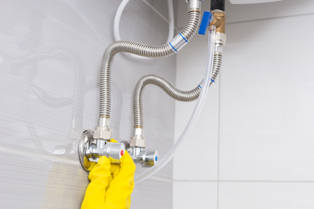 gloved: Close up detail view on yellow gloved hand checking ceiling mounted water tank valves in bathroom