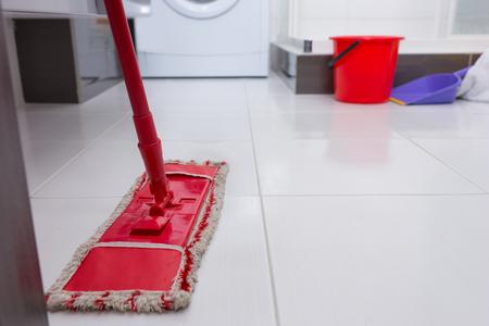 aseo: Colorido de la fregona roja en un suelo de baldosas blanco limpio con una lavadora, cacerola y cucharón visible detrás en un concepto de higiene y limpieza