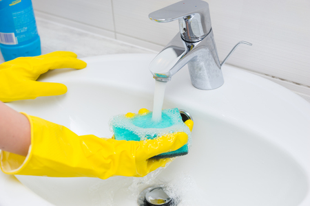 gloved: Housewife washing the hand basin in the bathroom with her gloved hands rinsing off a sponge under the flowing water from the tap or faucet, close up on her hands