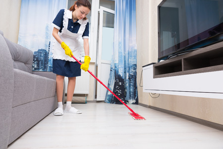 floor level: Maid or housekeeper in a neat white apron cleaning a living room floor with a colorful red mop, low angle view at floor level Stock Photo