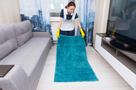 hotel suite: Housekeeper replacing and positioning a rug on a white tiled floor in an entertainment den or hotel suite Stock Photo