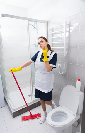 gloved: Pretty young housekeeper or maid relaxing on the job standing staring thoughtfully into the air as she cleans the bathroom with a mop