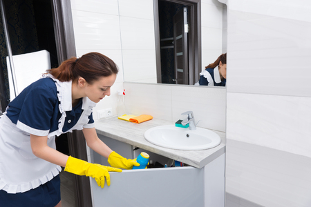 retrieving: Single housekeeper retrieving cleaning objects in sink