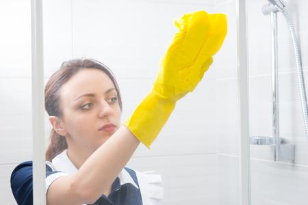 limpieza: La mujer joven con las manos enguantadas esponja abajo de una cabina de ducha de vidrio mientras se hace el trabajo de casa en un concepto de higiene y limpieza Foto de archivo