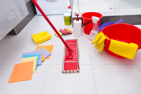 Display of assorted cleaning products on the clean white tiled floor in a bathroom with cloths, sponges, mop, bucket, basin and various chemicals and detergents 스톡 콘텐츠