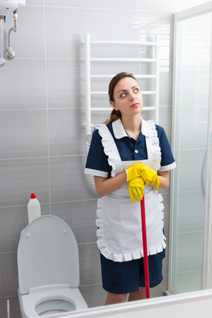 gloved: Thoughtful young maid or housekeeper taking a break from her work standing leaning on her mop staring into the air