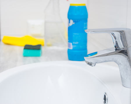 spigot: Close up of chrome sink spigot and cleaning chemicals, bottle, sponge and yellow rag with copy space