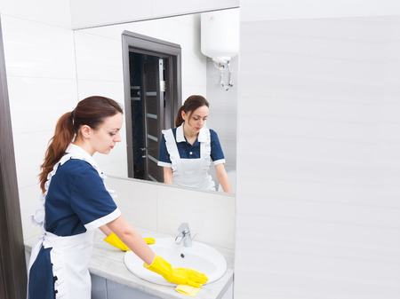 atomiser: Reflection of female housekeeping worker wearing yellow rubber gloves and white and blue uniform cleaning sink in bathroom Stock Photo