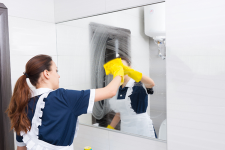 atomiser: Large hotel bathroom mirror smeared with detergent being cleaned up with yellow cloth by maid in blue and white uniform and yellow rubber gloves