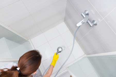 housekeeper: Vista de �ngulo alto de la hembra cabina de ducha de limpieza ama de casa con chorros de agua a lo largo de piso en el desag�e Foto de archivo