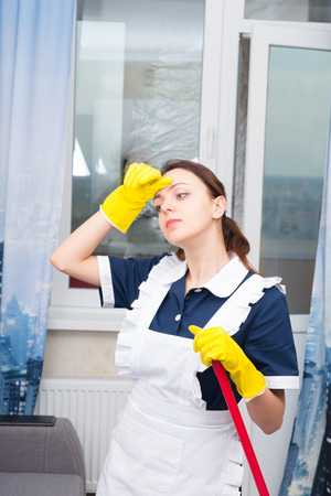 gloved: Tired hot housekeeper or maid standing holding a mop or broom wiping her forehead with a gloved hand, close up view
