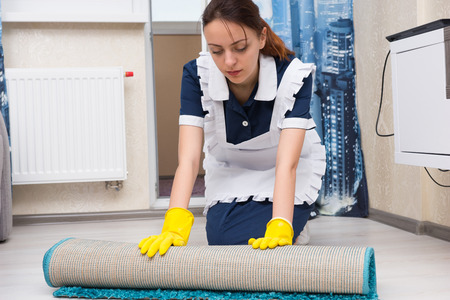rolling up: Maid or housekeeper doing the cleaning kneeling down and rolling up a small carpet to clean the tiles underneath in a house or hotel
