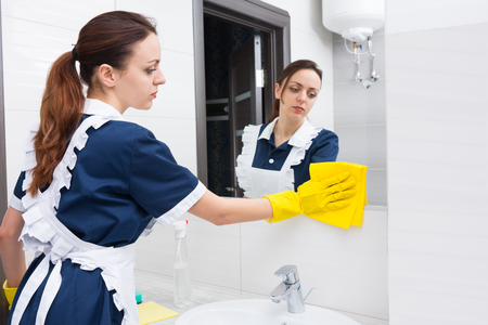 atomiser: Single young adult female hotel maid using yellow cloth and rubber gloves to tidy up low section of mirror in bright bathroom