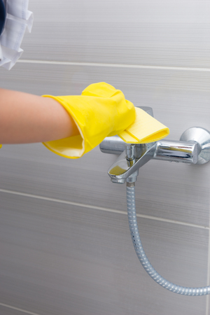 gloved: Maid or housewife cleaning the tap in a shower with her gloved hands and a soft absorbent cloth, cloth up view Stock Photo