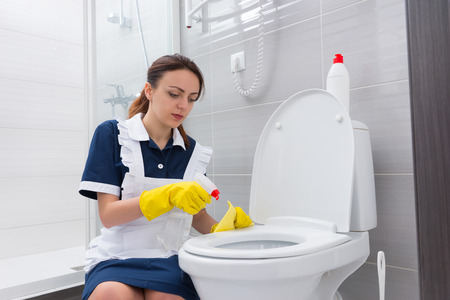 housekeeper: Kneeling female housekeeper with serious expression cleaning toilet set with spray bottle and yellow rag Foto de archivo