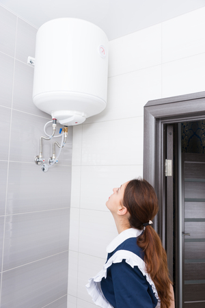 gloved: Single female hotel maid in ponytail and blue and white uniform inspecting ceiling mounted water tank in bathroom