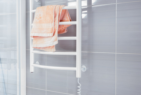 Empty bathroom with gray colored shower wall behind white metal warming rack with pink towel folded on top