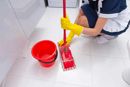 antibacterial soap: Housekeeper fitting a clean cloth to a mop as she cleans the floor in a white tiled bathroom in a home or hotel Stock Photo