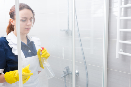 shower cubicle: Maid or housekeeper wearing a white apron and uniform cleaning a white bathroom spraying the glass shower cubicle with detergent with her gloved hands