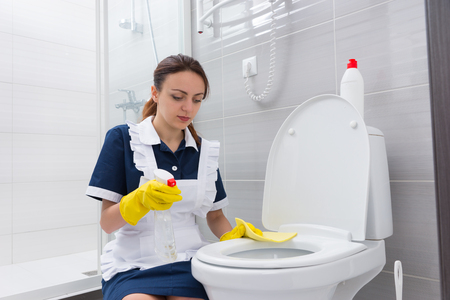 antibacterial soap: Single female maid with serious expression kneeling at toilet while cleaning seat with spray bottle and yellow rag in rubber gloved hands Stock Photo