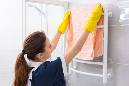 shower stall: Single hotel maid in blue and white uniform and yellow rubber gloves replacing towel on rack beside shower stall in bathroom