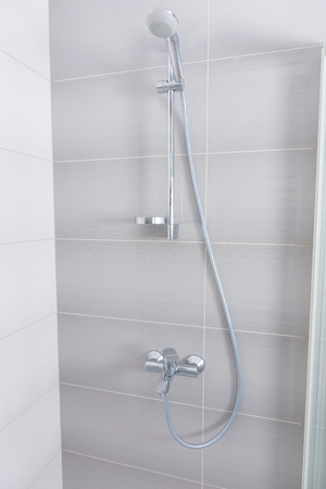 shower cubicle: Stainless steel and chrome shower fittings inside a grey tiled shower cubicle with glass door in an architectural background