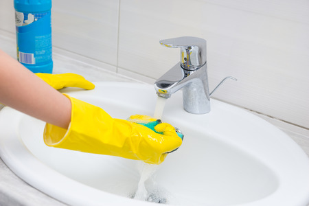 gloved: Housewife rinsing off a sponge for cleaning the bathroom under the running water from the hand basin, close up view of her gloved hands