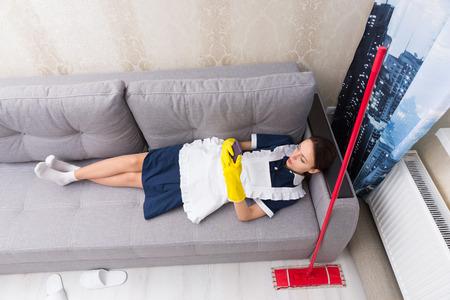 aseo: Lazy trabajo ama de casa tímida en uniforme de tomar un descanso acostada sobre su espalda en un sofá con su fregona al lado de su control de su teléfono móvil, vista desde arriba Foto de archivo