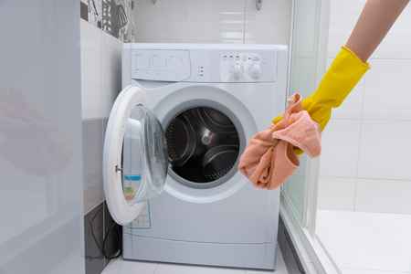 unidentifiable: Front view of unidentifiable yellow rubber gloved hand holding dirty pink towel in front of small front loading washing machine