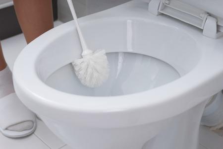 aseo: La mujer que limpia una taza de inodoro con un cepillo en una vista de primer plano conceptual de la higiene y la limpieza del hogar