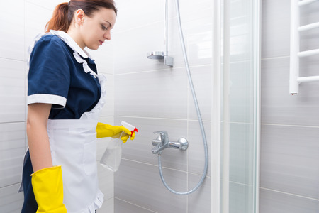 dispense: Housekeeper or maid cleaning a white shower using a spray bottle to dispense detergent , low angle side view in uniform
