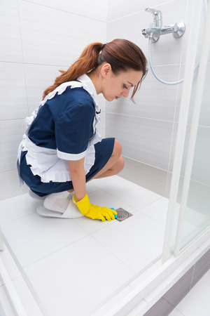 shower stall: Single female maid in blue dress, white apron and slippers kneeling inside shower stall while cleaning floor drain Stock Photo