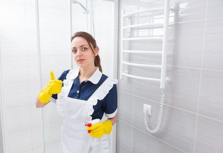 shower stall: Confident young female domestic worker standing in blue dress and white apron with thumbs up gesture while holding spray bottle next to shower stall in bathroom Stock Photo
