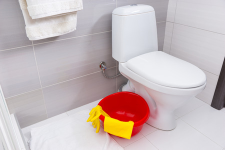 corner tub: Colorful red basin, yellow gloves and cloth for cleaning in a bathroom standing on the floor alongside a plain white toilet