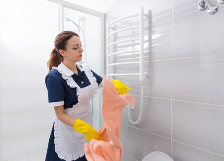 gloved: Single hotel housekeeper in blue and white uniform and yellow gloves removing pink towel from rack in bathroom